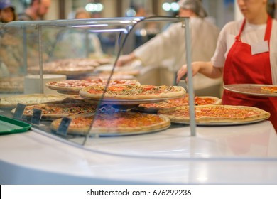 Variety of yummy pizzas under shopping window in pizzeria