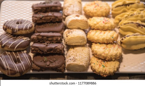 A variey of home made cookies or biscuits stacked on a silver baking tray or plate. An assorted or mix selection including chocolate, custard, coconut and butter biscuits. Ready to serve for Diwali.