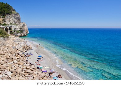 VARIGOTTI, LIGURIA - JUNE 2019: tourists sunbathing on the beach and take the bath into the Liguria's sea along the coast between Noli and Varigotti