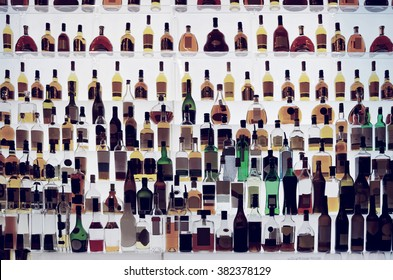 Various alcohol bottles in a bar, back light, all logos removed, toned