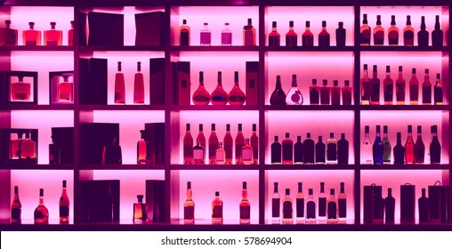 Various alcohol bottles in a bar, back light, all logos removed, toned image