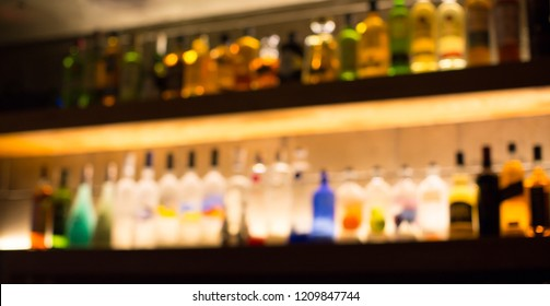 Various Alcohol Bottles and Beverages Lined up on Wall with Nice Lighting. Spirits and Liquor in a Bar. Back Light Blurred Defocused Restaurant. Pub with Alcoholic Beverages in Background Display.