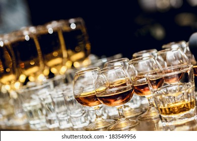 Various alcohol drinks standing on bar in snifters and shot glasses