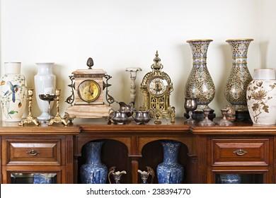Различные антикварные часы вазы и подсвечники на дисплее