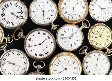 Various Antique pocket clocks on black background