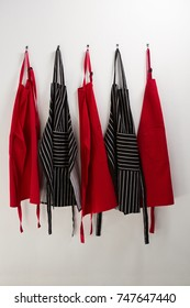 Various aprons hanging on hook against wall