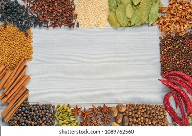 Various aromatic Indian spices and herbs on the gray kitchen table: star anise, fragrant pepper, cinnamon, turmeric, nutmeg, bay leaves, paprika. Spices texture background with copy space. Top view
