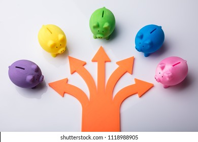 Various Arrow Symbols Showing Direction Towards Colorful Piggybanks Over White Background
