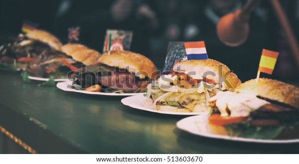 Various arts of burgers from different countries on a counter, street food or unhealthy food concept