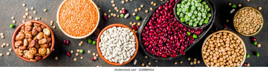 Various assortment of legumes - beans, soy beans, chickpeas, lentils, green peas. Healthy eating concept. Vegetable proteins. Dark concrete background copy space top view banner format