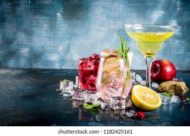 Various autumn winter seasonal alcohol cocktail Apple Rosemary, Cranberry vodka, Ginger lemon ale,  Almande Horchata, Kahlua Cacao, dark blue background copy space