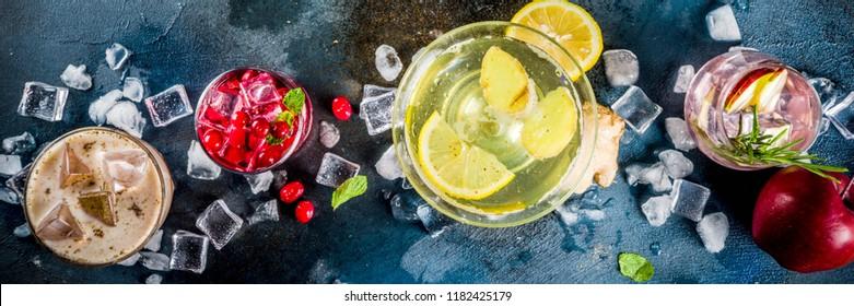Various autumn winter seasonal alcohol cocktail Apple Rosemary, Cranberry vodka, Ginger lemon ale,  Almande Horchata, Kahlua Cacao, dark blue background copy space top view banner