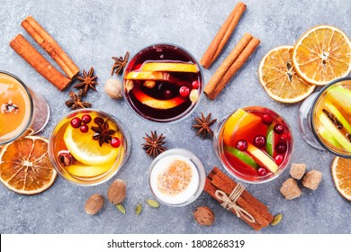 Various autumn or winter seasonal alcohol hot cocktails - mulled wine, glogg, grog, eggnog, warm ginger ale, hot buttered rum, punch, mulled apple cider on gray background, top view with copy space