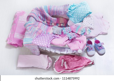 various baby clothes in a box on wooden table, top view