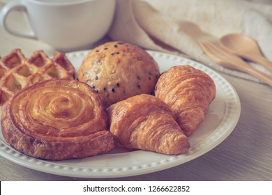 Various baked bread on plate and coffee cup