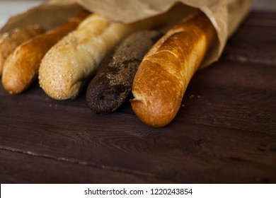Various baked breads on rustic wooden table. Close up.