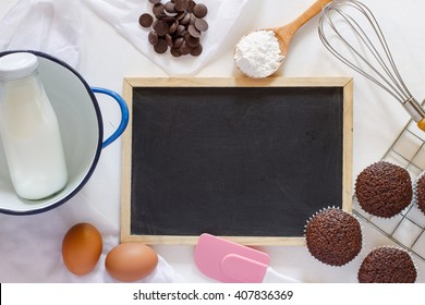Various of baking tool with chocolate muffin on white background and blackboard.