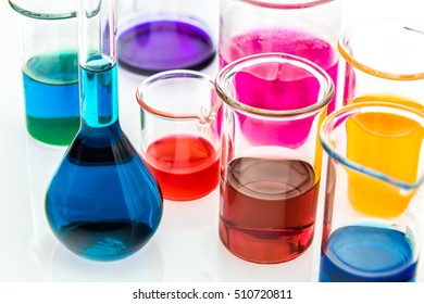 various beakers with different types of indicators in acids and basis, four colors of indicators in several solutions