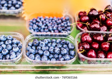 Various berries from a local farmer market.  Healthy local food market concept. Variety of berries in a box -  blackberry, raspberry, strawberry, cherry close up