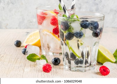 Various berry lemonade or mojito cocktails, fresh iced lemon lime raspberry blueberry infused water, summer healthy detox drinks light background copy space