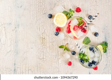 Various berry lemonade or mojito cocktails, fresh iced lemon lime raspberry blueberry infused water, summer healthy detox drinks light background copy space above