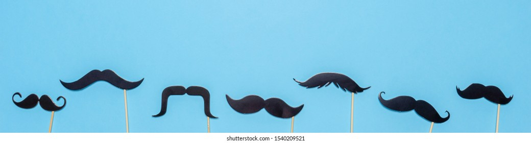 Various black photo booth props moustaches of different shape on blue background. Greeting card for father's day or men's health awareness month campaign concept. Flat lay, banner