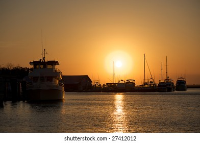 Various boats docked with the sun in full view