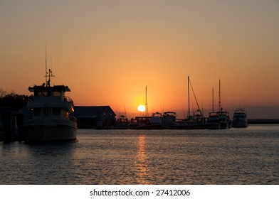 Various boats docked with the sun just above the horizon.