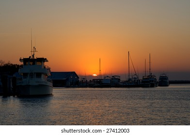 Various boats docked with the sun rising above the horizon.