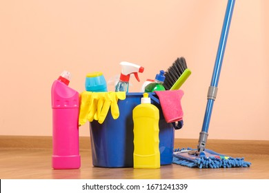 Various bottles with cleaning products and detergents, washcloths in a blue bucket and a mop in the room on the floor