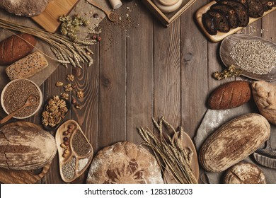 Various bread selection flat-lay. Top view of rye, wheat and multigrain rustic bread loaves over dark wooden vertical planks background with a blank copyspace for text in the middle of circle