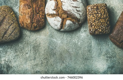Various bread selection flat-lay. Top view of Rye, wheat and multigrain rustic bread loaves over grey background, copy space, horizontal composition