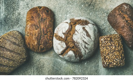 Various bread selection flat-lay. Top view of Rye, wheat and multigrain rustic bread loaves over grey concrete background
