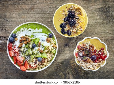 various breakfast smoothie bowls on wooden table, top view