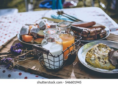 Various breakfast table with fruits egg and sausage, orange juice and milk