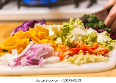 Various bright and colorful vegetables on wood cutting board, being prepared for a meal. Vegetables include red onion, white onion, squash, peppers, romanesco, and cabbage.