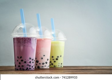 Various Bubble Tea in a plastic cups with drink straws on blue background. Take away drinks concept.