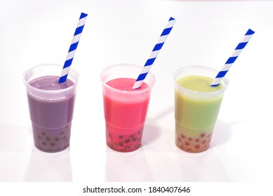 Various Bubble Tea in a row in plastic cups with drink straws isolated on white background. strawberry, mellon and taro bubble tea with juice balls