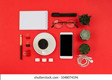 Various business accessories knolled on red background. Smartphone with black copyspace, coffee, glasses, succulents, notebook, clips, pen, headphones and marker. Mockup