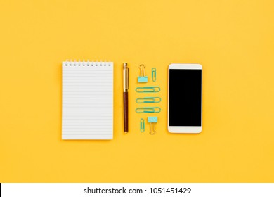 Various business and stationary accessories knolled on yellow