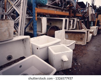 Various butler sinks and metal hardware piled in a salvage yard in the UK.