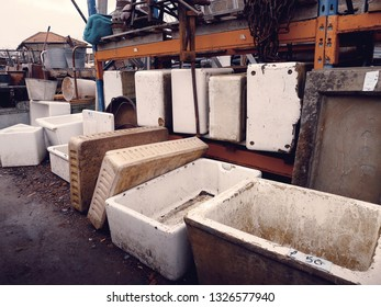 Various butler sinks piled in a salvage yard in the UK.