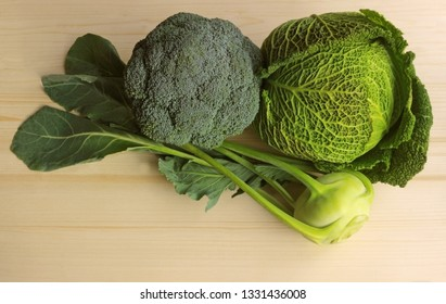various cabbages on bright wood: broccoli, kohlrabi and savoy cabbage