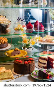 Various cakes with icing and desserts in refrigerated bakery case cabinet. Coconut shell dessert, chocolate cake and other sweets. Selective Focus