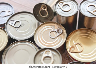 Various canned food in metal cans on wooden background , top view / canned goods non perishable food storage goods in kitchen home or for donations
