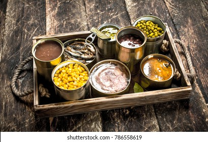 Various canned fruits, vegetables, fish and meat in tin cans on old tray. On a wooden background