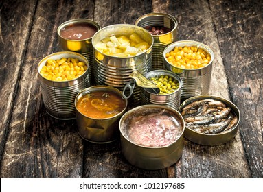 Various canned vegetables, meat, fish and fruits in tin cans. On a wooden background.