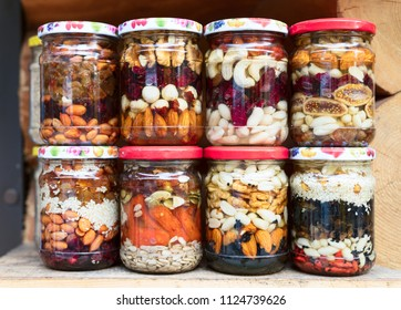 Various canned vegetables, nuts, and mushrooms in the glass jars.