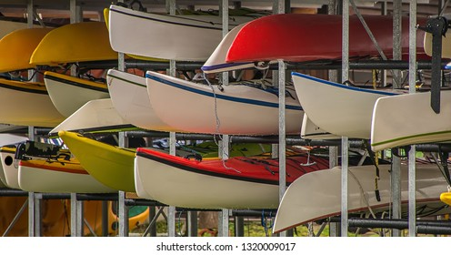 Various canoes have been stored in a steel rack. They are next to each other and stacked and are ready to be rented out to customers.