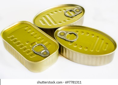 Various cans of canned unopened fish on white background